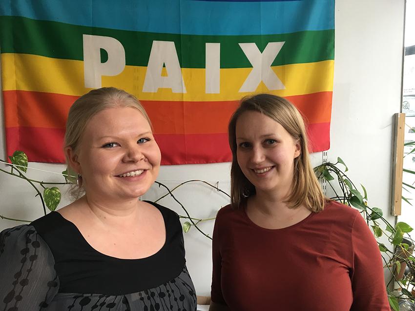 """Anni och Tuuli framför en flagga med ordet """"Paix""""."""