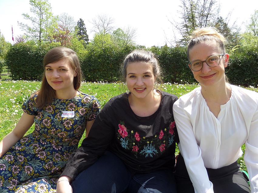 Katharina, Alissa och Nadja på en solig gräsmatta.