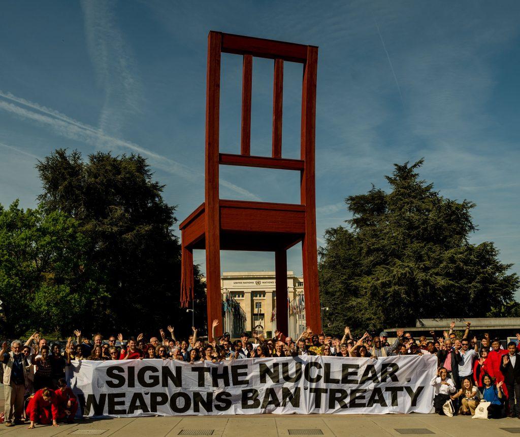 "Fredsaktivister med en banderoll: ""Sign the nuclear weapons ban treaty"", vid den stora stolen med ett trasigt ben vid FN i Genève."