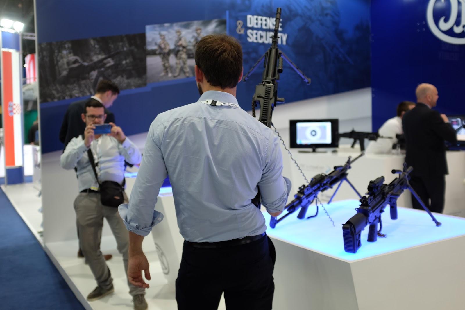 En man poserar med ett automatgevär i belgiska FN Herstals monter.